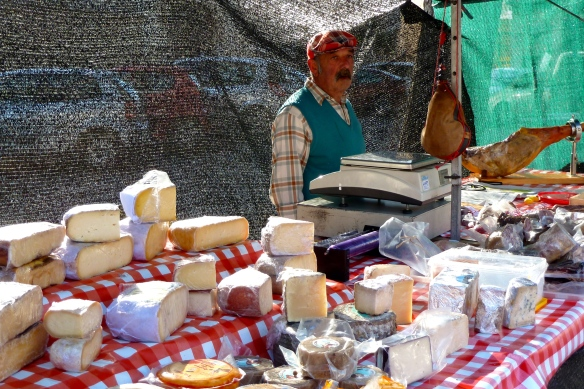 Glum, red-faced man selling cheeses and hams stands alone