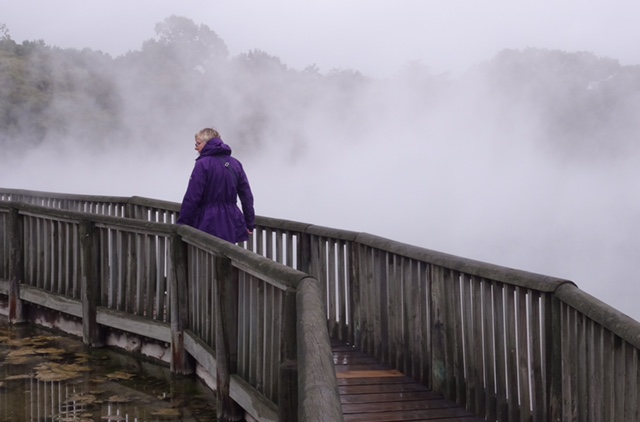 A boardwalk across a steaming pond in the park.