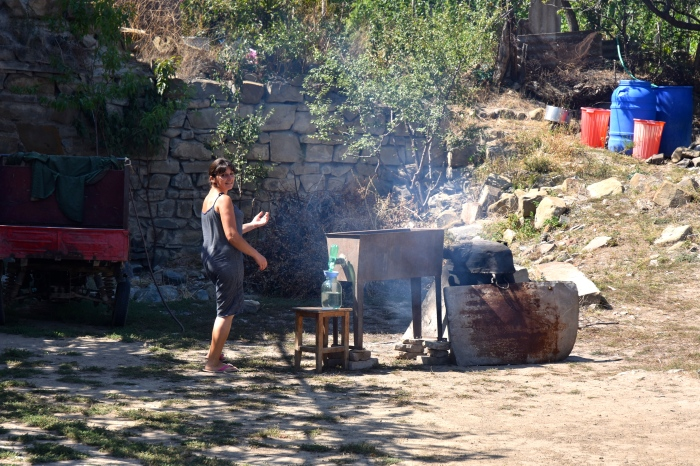 A woman distilling chat in her backyard